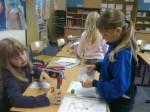 Jenny und Natalie bauen eine Brücke mit Steckwürfeln und Papier